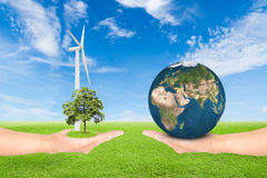 Green Earth concept. Hand holding tree with wind turbine and earth against green field and blue sky background.Elements of this image furnished by NASA Stock Image