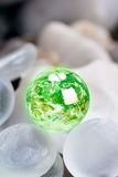 Green earth with glass stones. Concept suitable for environment protection themes, save the earth etc Stock Photography