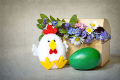 Green Easter egg, chicken toy and spring flowers Stock Image