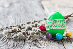 Green Easter egg decorated with lace and willow branch on wooden background. Selective focus Royalty Free Stock Images