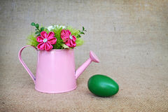 Green Easter egg and fabric flowers arranged in watering bucket Stock Photo