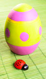 Easter egg. Green easter egg painted with color stripes and dots with wooden ladybugs  on green bamboo background Stock Photo