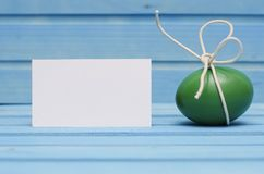 Green Easter egg with white bow on blue wooden background with blank card Royalty Free Stock Image