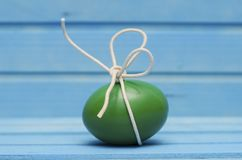 Green Easter egg with white bow on blue wooden background Royalty Free Stock Photo