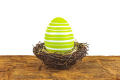 Green easter egg on a wooden table isolated on white royalty free stock photo
