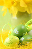 Green Easter eggs and daffodils Royalty Free Stock Photos