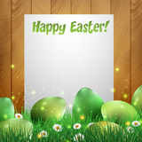 Green Easter eggs with a wooden background and white paper Stock Photo