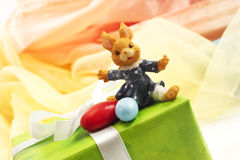 Green easter present with ribbon, easter bunny figure and sugar eggs Royalty Free Stock Photography