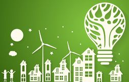Green eco city with dry tree in light bulb eco concept Stock Images