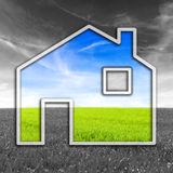 Green eco-friendly house. Concept of a green eco-friendly house with the simple outline of a home filled with green grass and blue sky in a greyscale landscape Royalty Free Stock Photo