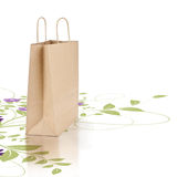 Green and eco friendly paper shopping bag. Kraft paper shopping bag isolated on a white background with a green floral design Stock Images