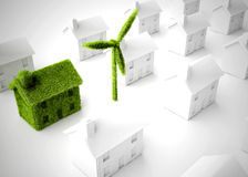 Green eco home. Environmental eco home with wind turbine among other non-eco homes Stock Image