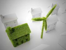 Green eco home. Environmental eco home with wind turbine among other non-eco homes Royalty Free Stock Photo
