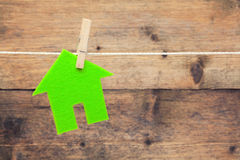 Green eco house. Attach to rope with clothes pins on wooden background Stock Photography