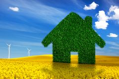 Green, ecological house, real estate concept. Spring land, blue sky, wind turbines. Clean energy, environment Stock Photos