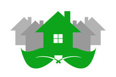 Green ecology house and grey houses. Green ecological house is standing on two green leaves. Gray houses are standing behind the green house. Isolated on the royalty free illustration