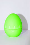 Green egg timer in front of white background Stock Images