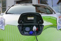 Green electric car charging on the street. Front of electric car with power plug charging its batteries Royalty Free Stock Photo