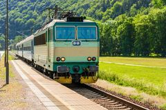 A green electric locomotive passing the Czech countryside Stock Images