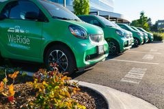 Green electric vehicles on the parking lot stock image