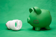 Green Electricity. New energy saving lightbulb with piggy bank on green fabric background. Piggy bank has a lipstick kiss mark Stock Photos