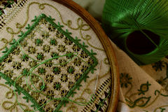 Green embroidery. Pattern embroidered with green threads on rough linen fabric, an antiquarian, round Royalty Free Stock Image