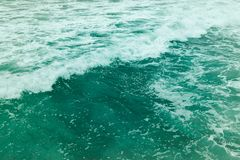 Green emerald color water. Wallpaper. Wallpaper with green color sea water and white waves stock photography