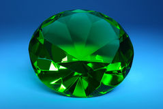 Green emerald on a dark blue background. Stock Photography