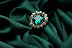 Green emerald fashion engagement diamond ring. On green satin background. Luxury female jewellery, close-up. Selective focus royalty free stock photo