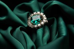 Green emerald fashion engagement diamond ring. On green satin background. Luxury female jewellery, close-up. Selective focus stock image