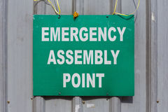 Green Emergency Assembly Point sign mounted to a metal fence. Royalty Free Stock Photos