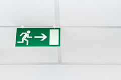 Green emergency exit sign. On a white wall Stock Photo
