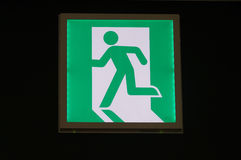 Green emergency exit sign. In black background Stock Photo