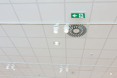Green emergency exit sign on ceiling, modern light, hatch for co Stock Images