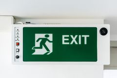 Emergency exit sign. Direction to the escape way. Green emergency exit sign. Direction to the escape way Royalty Free Stock Image