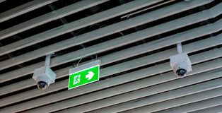 Green emergency exit sign. Direction to the escape way and CCTV. Hanging on wood ceiling Stock Photos