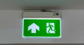Green emergency exit sign. Direction to the escape way. Green emergency exit sign. Direction to the escape way on white background Royalty Free Stock Photo