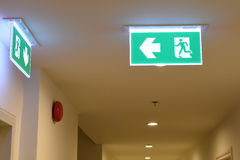 Green emergency exit sign showing the way to escape.  Royalty Free Stock Photo
