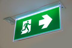 Green emergency exit sign showing the way to escape.  Royalty Free Stock Image