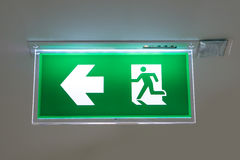 Green emergency exit sign showing the way to escape.  Royalty Free Stock Photography