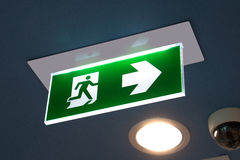 Green emergency exit sign showing the way to escape. Green emergency exit sign showing the way to escape Stock Photos