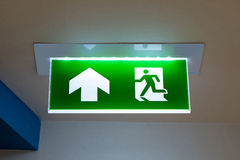 Green emergency exit sign showing the way to escape. Green emergency exit sign showing the way to escape Royalty Free Stock Images