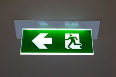 Green emergency exit sign showing the way to escape. Green emergency exit sign showing the way to escape Royalty Free Stock Image