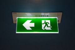 Green emergency exit sign showing the way to escape. Green emergency exit sign showing the way to escape Stock Photo