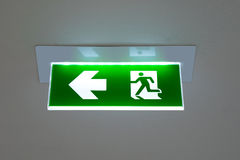 Green emergency exit sign showing the way to escape. Green emergency exit sign showing the way to escape Royalty Free Stock Photo