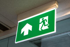 Green emergency exit sign showing the way to escape. Green emergency exit sign showing the way to escape Royalty Free Stock Photos