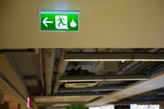 Green emergency exit sign showing the way to escape. Fire exit in the building Stock Images