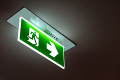 Green emergency exit sign showing the way to escape. Green emergency exit sign showing the way to escape Stock Images