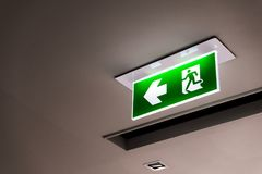 Green emergency exit sign showing the way to escape. Green emergency exit sign showing the way to escape Stock Photography