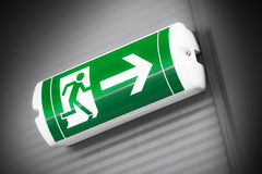 Green emergency exit sign showing the way to escape Stock Image